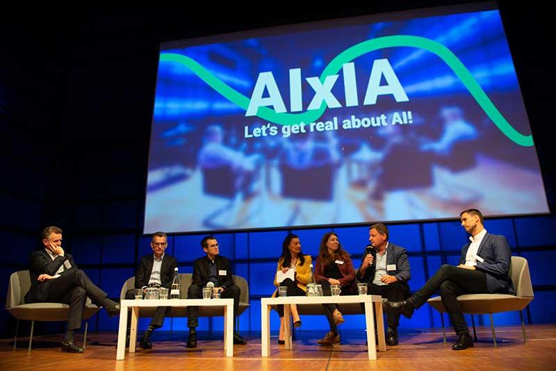 Menschen auf der Bühne: Paneldiskussion bei der AIxIA in Karlsruhe. Bild:  DIZ | Digitales Innovationszentrum, aixia.eu