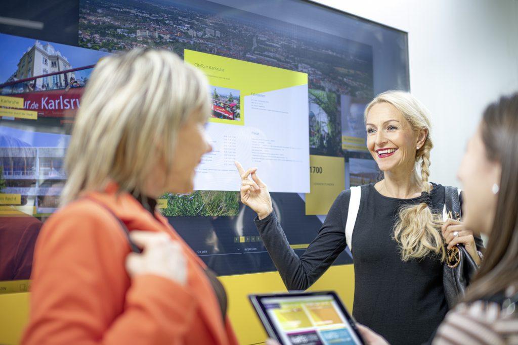 Eine Frau zeigt zwei Personen etwas auf einem großen Display. Bild: KTG Karlsruhe Tourismus GmbH