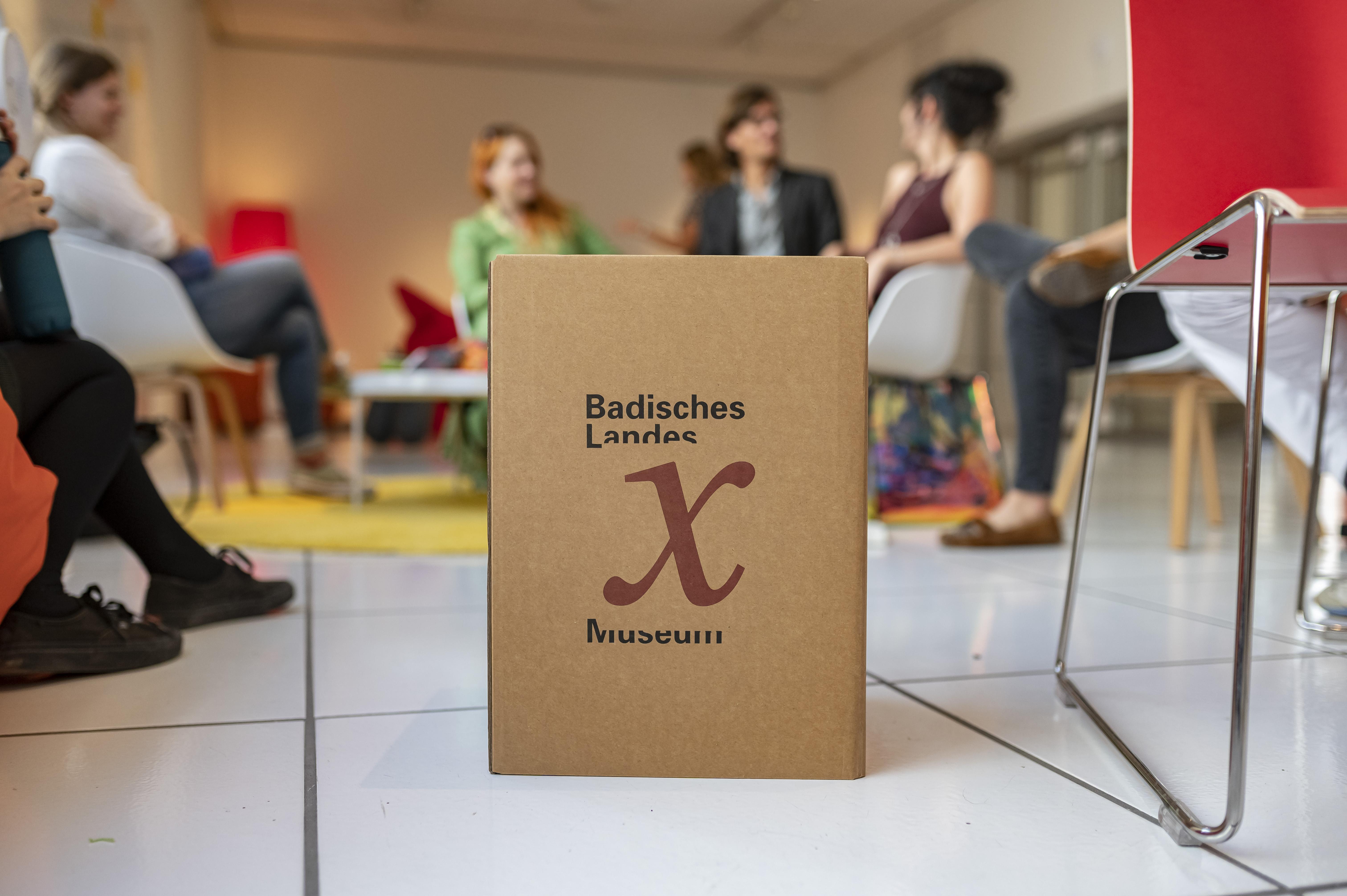 Menschen sitzen im Halbkreis und unterhalten sich, im Vordergrund eine Kiste mit der Aufschrift museum x. © Badisches Landesmuseum - Foto ARTIS - Uli Deck