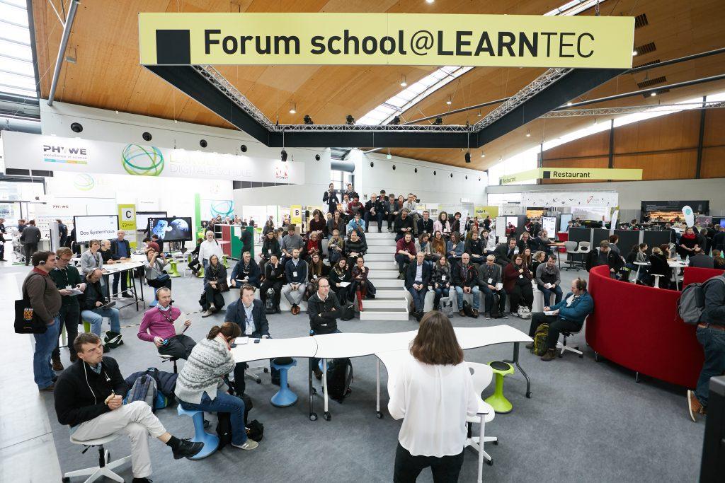 """Unter einem Schild mit der Aufschrift """"Forum school @Learntec"""" sitzen viele Menschen und lauschen einem Vortrag. Bild: Messe Karlsruhe / Behrendt und Rausch"""