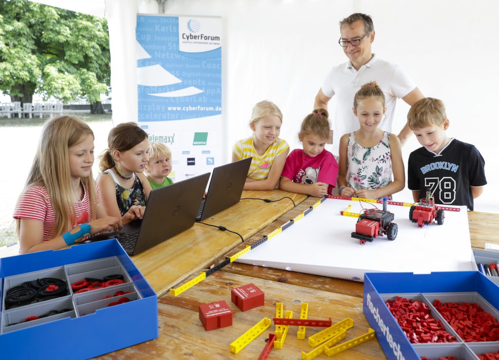 Eine Gruppe Kinder programmiert an Rechnern fischertechnik-Fahrzeuge. Bild: Jürgen Rösner