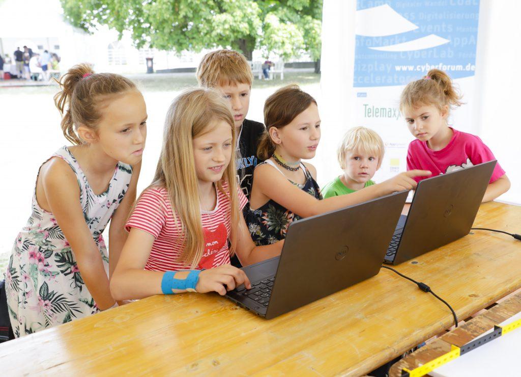 Mehrere Kinder arbeiten interessiert an zwei Laptops.  Bild: EFFEKTE, Jürgen Rösner