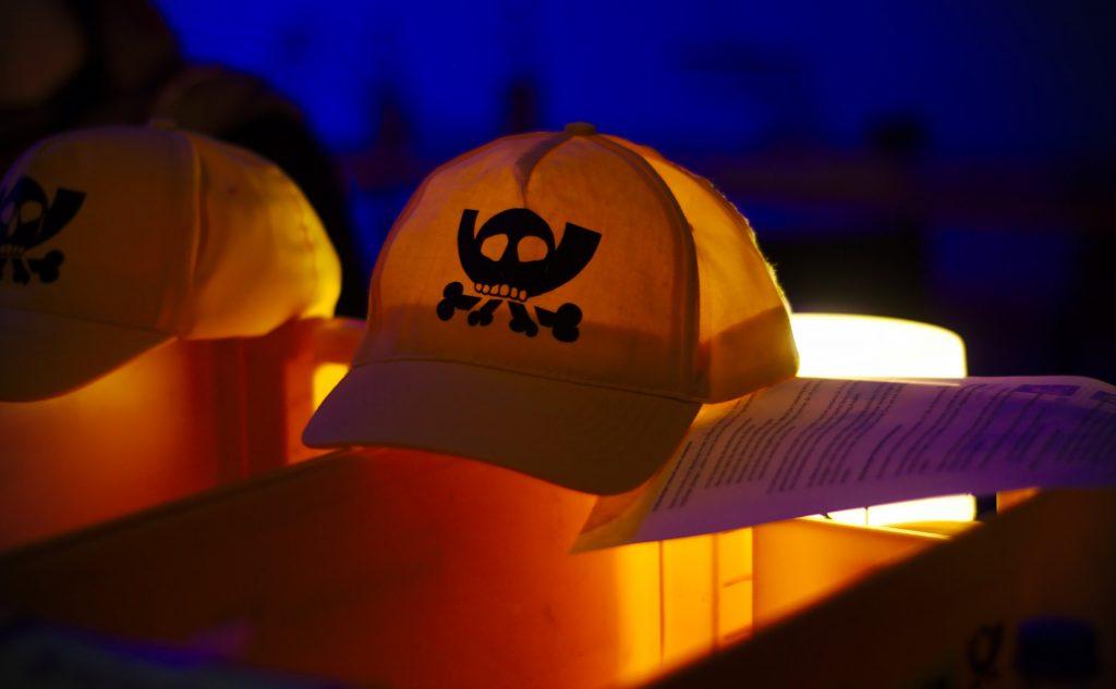Zwei gelbe Mützen, die von hinten beleuchtet sind. Auf den Mützen ist das sogenannte Pesthörnchen gedruckt, das Logo des CCC. Bild: @ElektrollArt