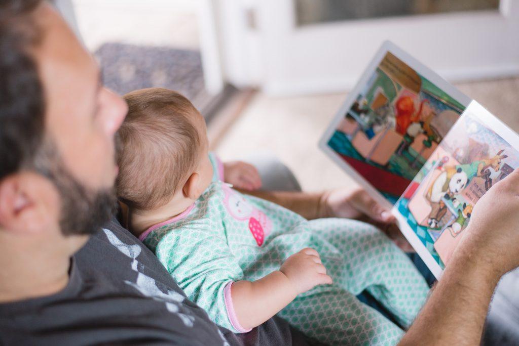Ein Mann schaut mit einem Kleinkind ein Bilderbuch an. Bild: Picsea on Unsplash