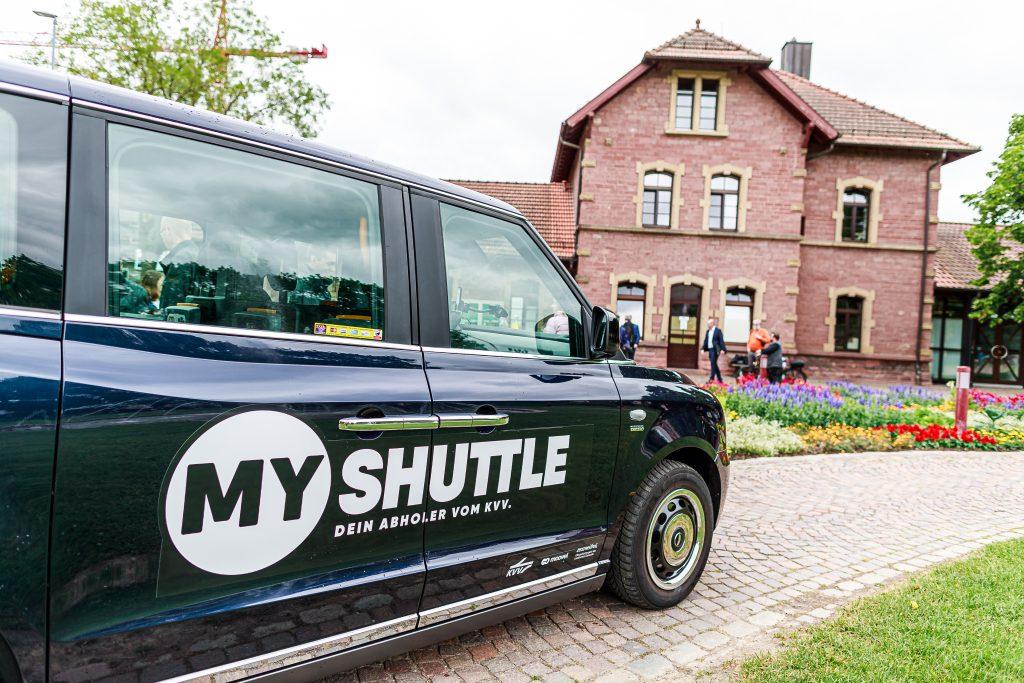 Ein schwarzer KVV Shuttle vor einem Haus